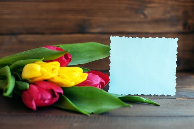 Fiori e una carta di benvenuto su fondo di legno scuro. Foto Premium