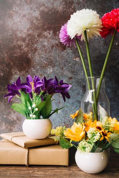 Fiori finti in diversi tipi di vaso con scatole regalo avvolto su sfondo grunge Foto Gratuite