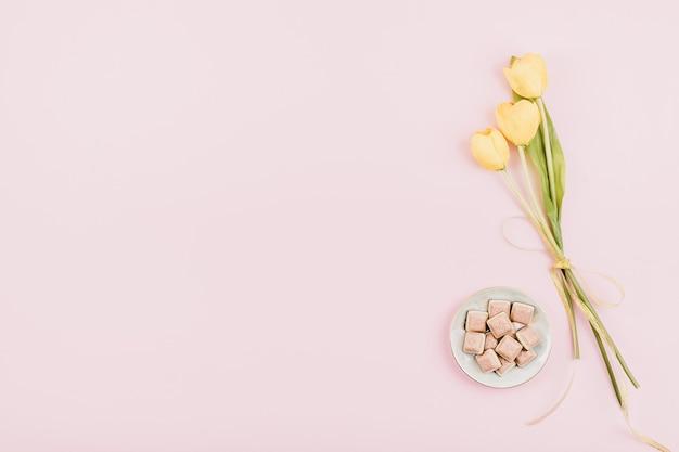 Fiori gialli dei tulipani e cioccolato rosa su fondo pastello. piatto compleanno festa festiva Foto Premium