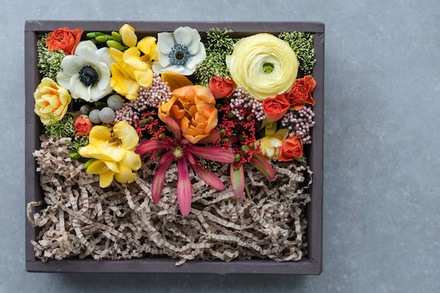 Fiori in giftbox su sfondo grigio. mazzo di vari fiori in vecchia scatola rustica di legno, vista superiore. Foto Premium