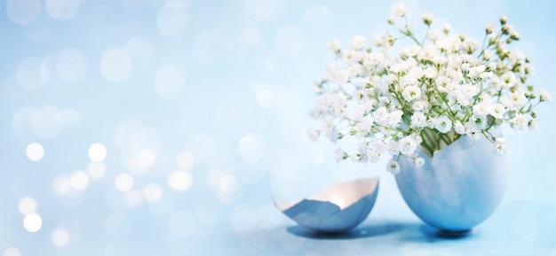 Fiori in un uovo di pasqua blu con luci bokeh Foto Premium