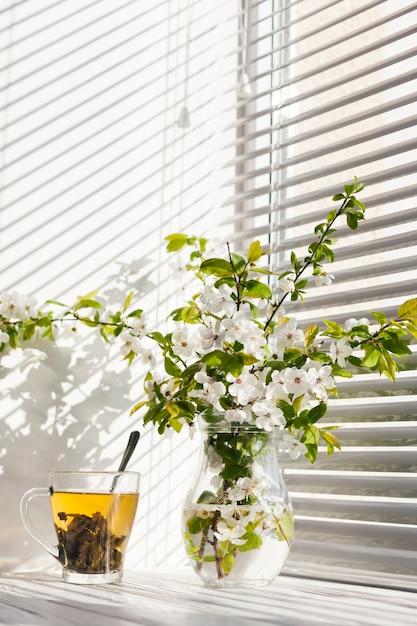 Fiori in un vaso con una tazza di tè Foto Gratuite