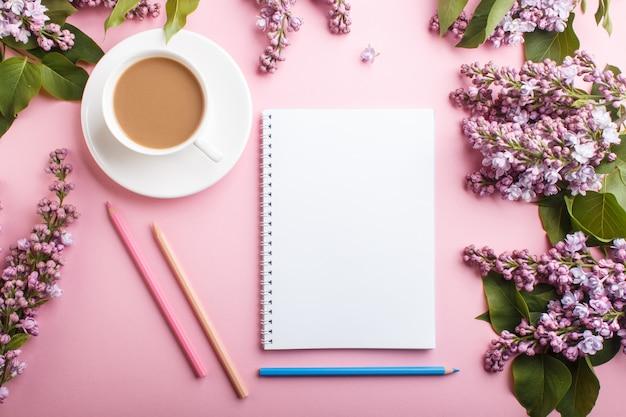 Fiori lilla viola e una tazza di caffè con il taccuino e matite colorate su sfondo rosa pastello Foto Premium