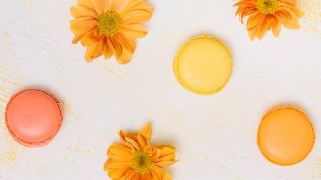 Fiori luminosi con biscotti sul tavolo Foto Gratuite