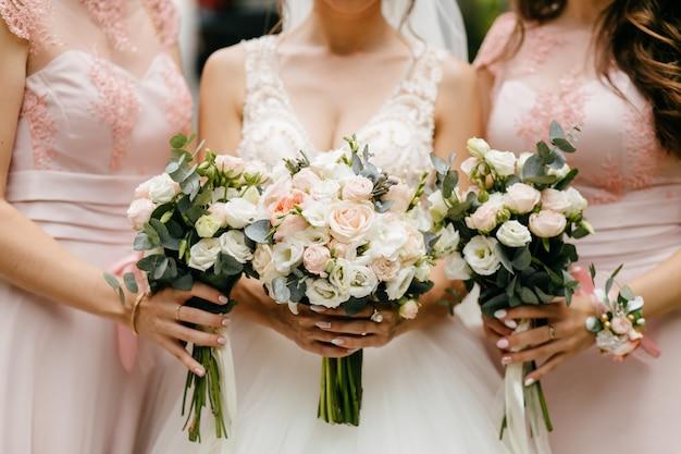 Fiori matrimonio, sposa e damigelle che tengono i loro mazzi al giorno delle nozze Foto Gratuite