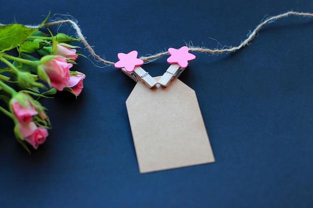 Fiori, mollette decorative e carta per appunti su uno sfondo scuro. concetto di congratulazioni per la vacanza Foto Premium
