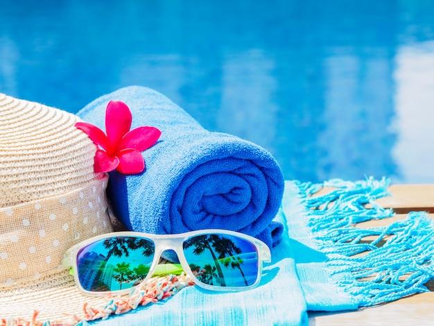 Fiori, occhiali da sole, cappello da spiaggia e asciugamano blu sul lato della piscina. Foto Premium