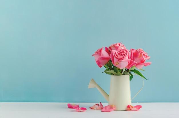 Fiori rosa appassiti all'annaffiatoio su fondo di legno bianco e blu Foto Premium