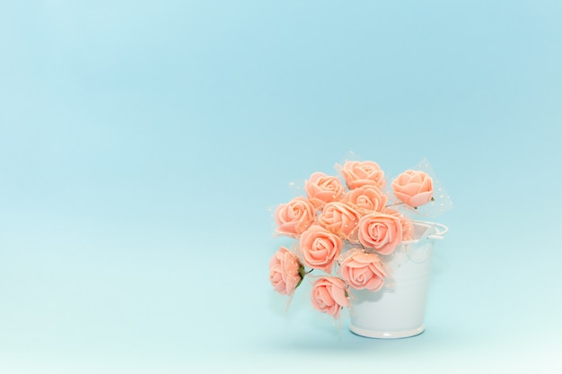 Fiori rosa in un secchio bianco giocattolo su uno sfondo azzurro, fiori per la vacanza Foto Premium