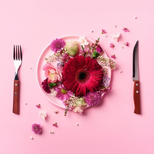 Fiori rosa sul piatto rosa, forchetta, coltello su incisivo sfondo pastello. Foto Premium