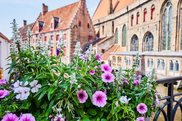 Fiori sopra il fiume vicino al campanile a bruges belgio Foto Premium
