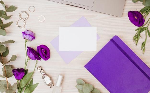 Fiori viola eustoma; orecchini; anelli; diario; orologio da polso e smalto per unghie sulla scrivania in legno Foto Gratuite