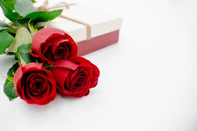 Fiorisce la composizione con il contenitore di regalo fatto dei fiori di rosa su fondo bianco Foto Premium