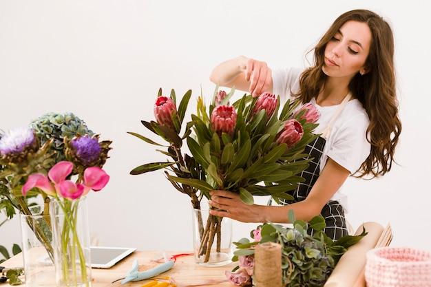 Fiorista del colpo medio che sistema il mazzo dei fiori Foto Gratuite