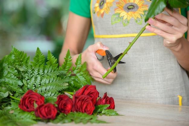 Fiorista della donna che prepara i fiori del mazzo. Foto Premium
