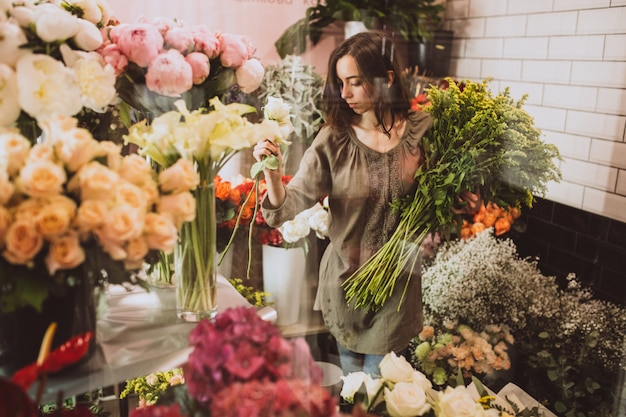 Fiorista donna nel suo negozio floreale prendersi cura dei fiori Foto Gratuite