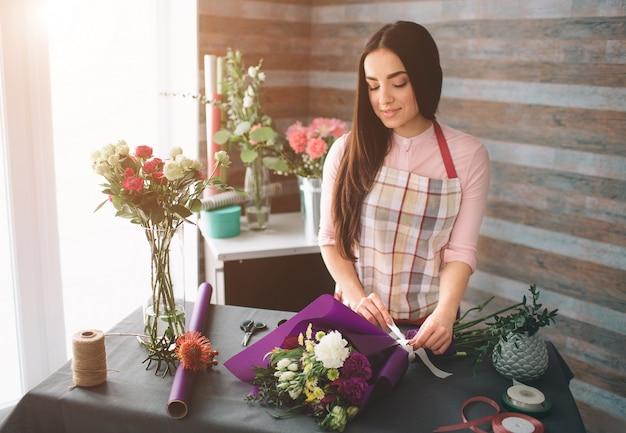 Fiorista femminile al lavoro: bella giovane donna dai capelli scuri che fa moda bouquet moderno di fiori diversi. donne che lavorano con i fiori in officina Foto Premium