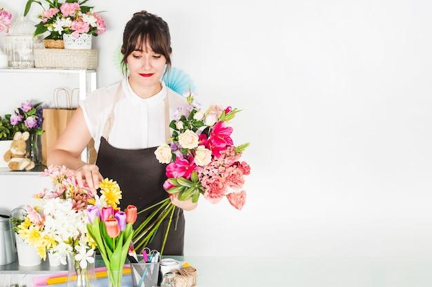 Fiorista femminile che ordina i fiori in negozio floreale Foto Gratuite