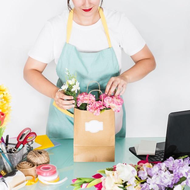Fiorista femminile che organizza i fiori in sacco di carta Foto Gratuite