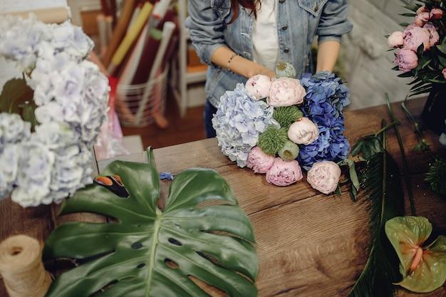 Fiorista in un negozio di fiori che fa un mazzo di fiori Foto Gratuite