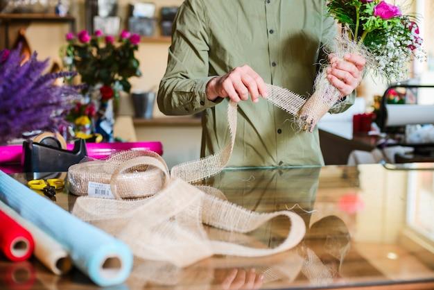 Fiorista maschio che fa mazzo nel negozio di fiore Foto Premium