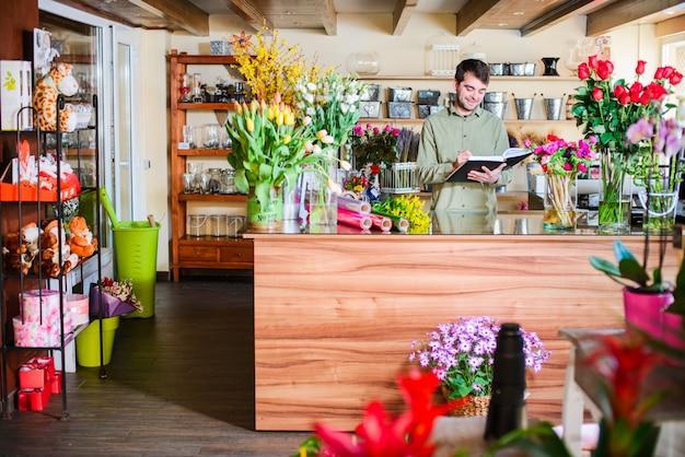 Fiorista maschio che prende le note in un negozio di fiore Foto Premium
