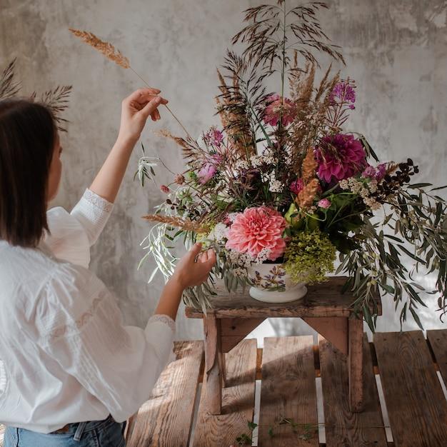 Fiorista professionista femminile prepara la composizione di fiori selvatici Foto Premium