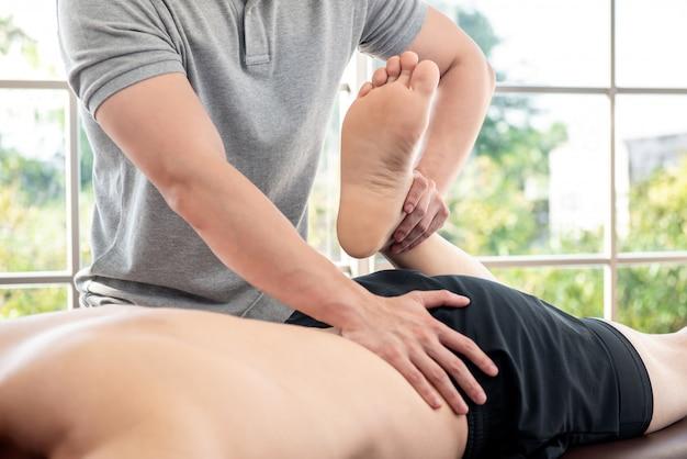Fisioterapista che dà massaggio e che allunga al paziente maschio dell'atleta Foto Premium
