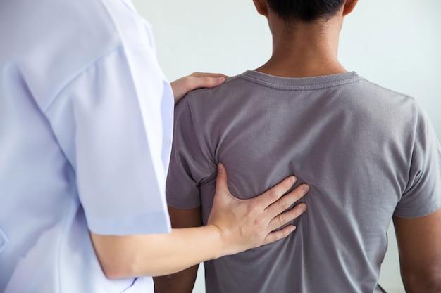 Fisioterapista che fa un trattamento curativo sulla schiena dell'uomo. Foto Premium