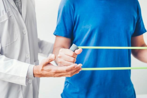 Fisioterapista uomo dando il trattamento di esercizio banda di resistenza circa i muscoli del petto e la spalla del paziente maschile atleta concetto di terapia fisica Foto Premium