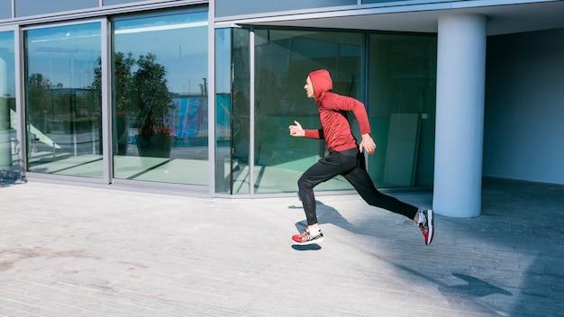 Fitness giovane corridore maschio in esecuzione all'esterno dell'edificio Foto Gratuite
