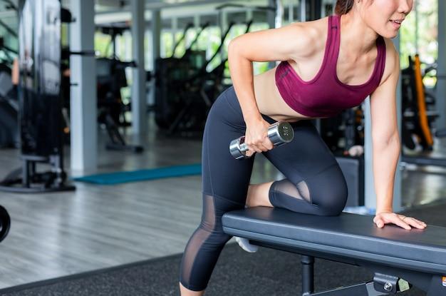Fitness ragazza asiatica sollevamento manubri in palestra. Foto Premium