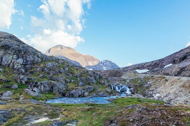 Fiume che scorre attraverso il paesaggio di montagna di roccia in estate Foto Gratuite
