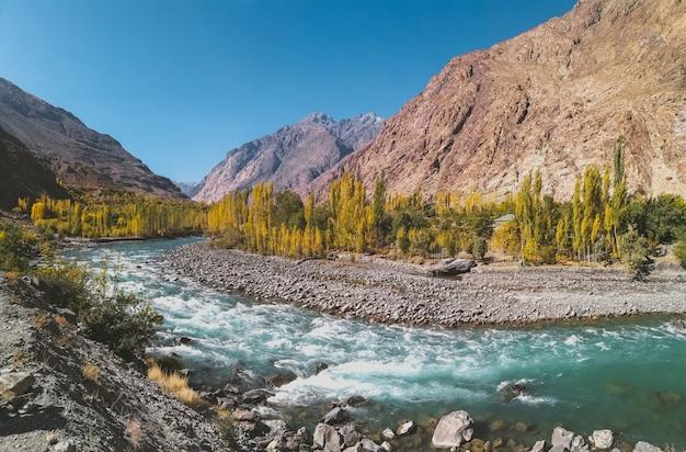 Fiume gilgit che scorre attraverso gupis, con una vista di catena montuosa e alberi in autunno. Foto Premium