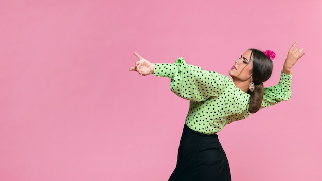 Flamenca del colpo medio che esegue floreo su fondo rosa Foto Gratuite
