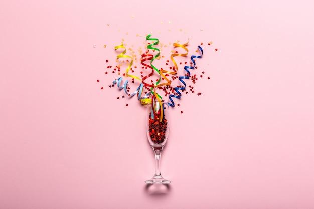 Flat lay of celebration. bicchiere di champagne con stelle filanti colorate Foto Premium