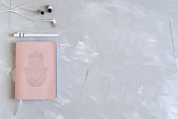 Flatlay con blocco note, penna e cuffie. pianifica la tua attività. taccuino rosa su sfondo grigio Foto Premium