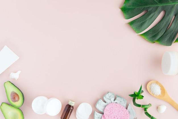 Flatlay di cosmetici spa con bambù, sale da bagno, crema e asciugamano su rosa pastello Foto Premium