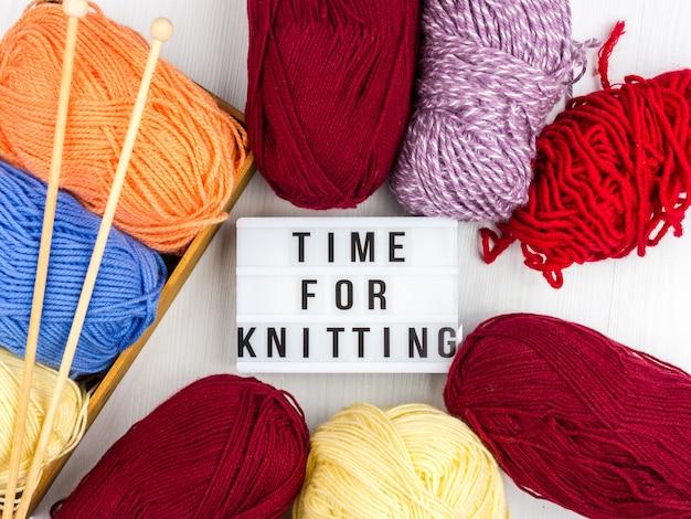 Flatlay di matasse multicolori di filato e ferri da maglia con scritte - tempo di lavorare a maglia Foto Premium