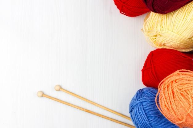 Flatlay di multicolore pastello tricottare matasse di filati e ferri da maglia su sfondo bianco Foto Premium