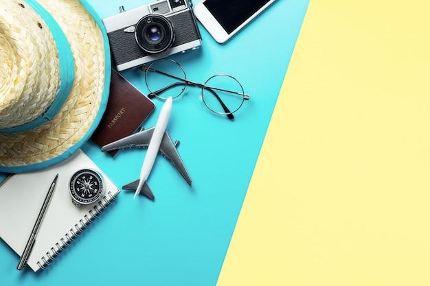 Flatlay di vista superiore degli oggetti e dei dispositivi degli accessori di viaggio su fondo rosa giallo blu Foto Premium