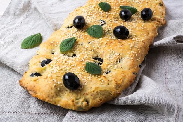Focaccia di pane italiano con oliva, aglio ed erbe sul tovagliolo di lino Foto Premium