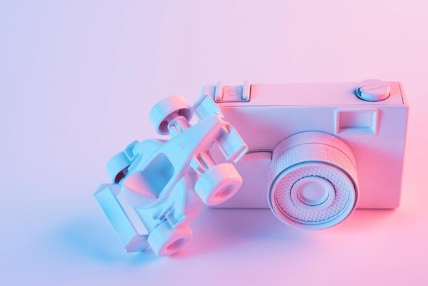 Focus della luce sulla macchina di formula uno sopra la telecamera su sfondo rosa Foto Gratuite