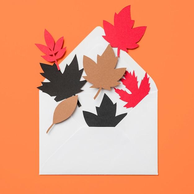 Fogli di autunno di carta in busta su priorità bassa arancione Foto Gratuite