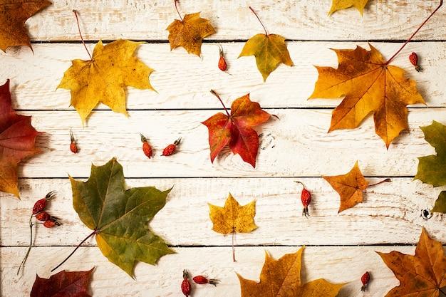Fogli di autunno variopinti su superficie di legno. vista dall'alto Foto Premium