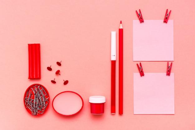 Fogli di cancelleria per appunti ritagliati, matita, pennarello, tempera, plastilina e cera su una vista superiore verde Foto Premium