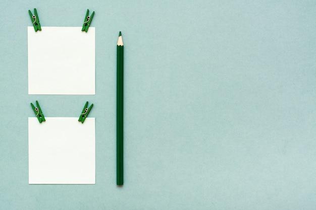 Fogli per appunti con clip e una matita su una vista superiore verde Foto Premium