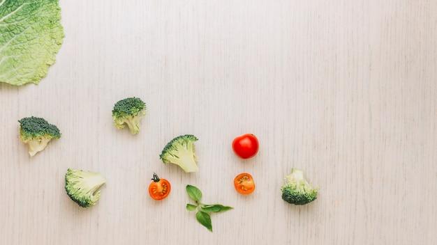 Foglia di cavolo; broccoli; basilico e pomodorini su superficie di legno Foto Gratuite