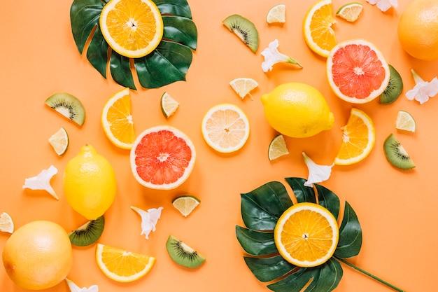 Foglie con arance vicino frutta e fiori Foto Gratuite