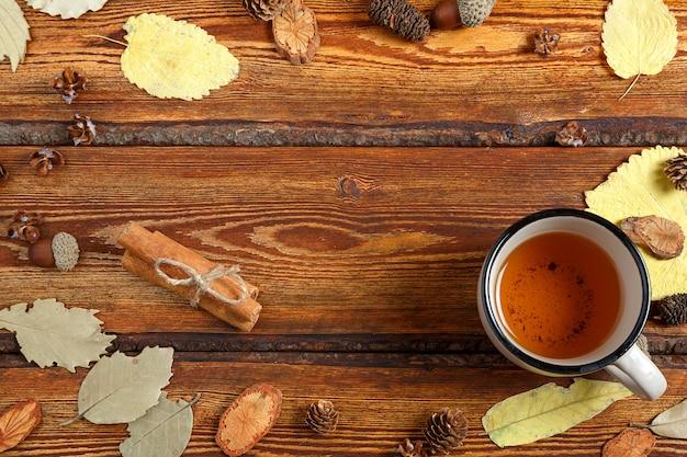 Foglie di autunno gialle e un bicchiere di tè su un vecchio fondo di legno scuro con uno spazio in bianco per testo Foto Premium